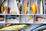Open tackle box with brightly coloured lures